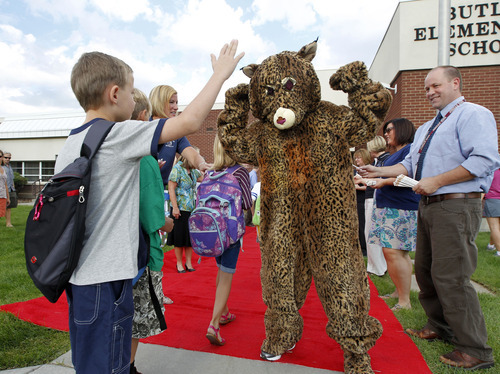 Al Hartmann  |  The Salt Lake Tribune Canyon School District Butler Elementary School students get a high five from the Bobcat school mascot as they walk down a red carpet to enter the front doors of the school Monday.   They passed by cheering teachers, staff members and the school's Bobcat mascot in a lively welcome back to school.