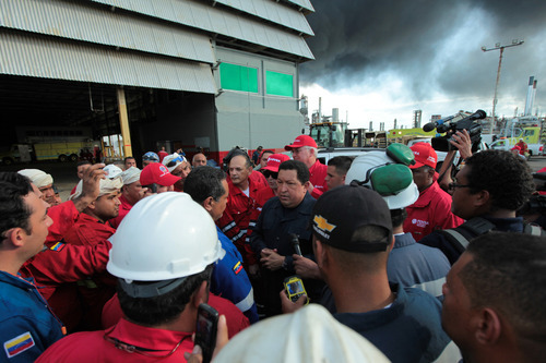 In this photo provided by Miraflores Presidential Press Office, Venezuela's president Hugo Chavez, center, speaks with workers during a visit to the Amuay refinery near Punto Fijo, Venezuela, Sunday, Aug. 26, 2012. A huge explosion rocked Venezuela's biggest oil refinery early Saturday killing at least 39 people and injuring more than 80 in Venezuela's deadliest refinery blast ever. (AP Photo/Miraflores Presidential Office)