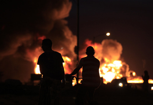 Two boys look at flames rising from the Amuay refinery after an explosion near Punto Fijo, Venezuela, Sunday, Aug. 26, 2012. Venezuelans who live next to the country's biggest oil refinery said they smelled a strong odor of sulfur hours before a gas leak ignited in an explosion on Saturday that killed at least 39 people and injured more than 80. (AP Photo/Ariana Cubillos)