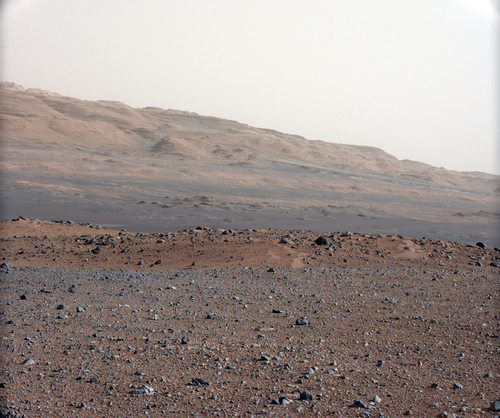 In this image released by NASA on Monday, Aug. 27, 2012, an image taken by the Mast Camera (MastCam) highlights the geology of Mount Sharp, a mountain inside Gale Crater, where the rover landed. Prior to the rover's landing on Mars, observations from orbiting satellites indicated that the lower reaches of Mount Sharp, below the line of white dots, are composed of relatively flat-lying strata that bear hydrated minerals. Those orbiter observations did not reveal hydrated minerals in the higher, overlying strata. The MastCam data now reveal a strong discontinuity in the strata above and below the line of white dots, agreeing with the data from orbit. Strata overlying the line of white dots are highly inclined (dipping from left to right) relative to lower, underlying strata. The inclination of these strata above the line of white dots is not obvious from orbit. This provides independent evidence that the absence of hydrated minerals on the upper reaches of Mount Sharp may coincide with a very different formation environment than lower on the slopes. The train of white dots may represent an