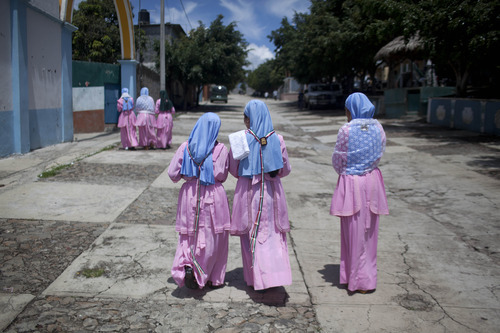 People belonging to the Virgen del Rosario religious group, walk on the main road of Nueva Jerusalen, Mexico, Sunday, Aug. 26, 2012. Mexican authorities are still unable to overcome the resistance of this religious sect in western Mexico which has refused to allow public school teachers to hold classes in their town (AP Photo/Alexandre Meneghini)