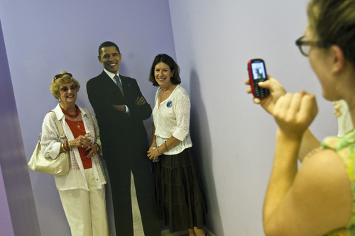 Chris Detrick  |  The Salt Lake Tribune Volunteer Maureen Haley takes a picture of Maxine C. Babalis and Stephanie Kesterson with a cardboard cutout of President Obama at the Utah headquarters for the Obama for President campaign located at 175 West 200 South in Salt Lake City Tuesday August 28, 2012.
