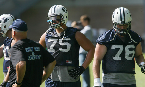 Steve Griffin | The Salt Lake Tribune   BYU lineman, Braden Brown, center, and Braden Hansen, right, run drills during a practice Aug. 6, 2012.