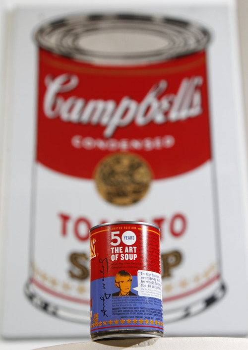 In this photograph taken Aug. 24, 2012,  a new limited edition Campbell's tomato soup can with art and sayings by artist Andy Warhol is displayed in front of an original Warhol Pop Art painting from the 1960's in the boardroom at Campbell Soup Company in Camden, N.J. Campbell plans to introduce the special-edition cans of its condensed tomato soup bearing labels reminiscent of the pop artist's paintings at Target stores starting Sunday, Sept. 2, 2012. (Photo/Mel Evans)