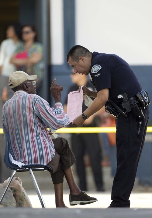 Senior driver Preston Carter, 100, left, talks with a police officer, after police say his car went onto a sidewalk and plowed into a group of parents and children outside a South Los Angeles elementary school, Wednesday, Aug. 29, 2012, in Los Angeles. Nine children and two adults were injured in the wreck. (AP Photo/Damian Dovarganes)