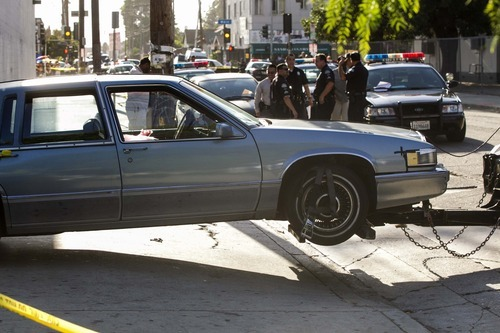 A Cadillac car that was driven by Preston Carter, 100, not seen, is towed away after police say the car went onto a sidewalk and plowed into a group of parents and children outside a South Los Angeles elementary school, Wednesday, Aug. 29, 2012, in Los Angeles. Nine children and two adults were injured in the wreck. (AP Photo/Damian Dovarganes)