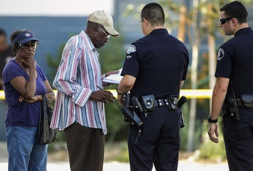 Preston Carter, 100, left, signs a police citation after police say his car went onto a sidewalk and plowed into a group of parents and children outside a South Los Angeles elementary school, Wednesday, Aug. 29, 2012, in Los Angeles. Nine children and two adults were injured in the wreck. (AP Photo/Damian Dovarganes)