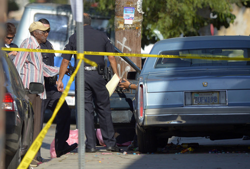 Preston Carter, left, 100, talks with police officers after police say his car went onto a sidewalk and plowed into a group of parents and children outside a South Los Angeles elementary school, Wednesday, Aug. 29, 2012, in Los Angeles. Nine children and two adults were injured in the wreck. (AP Photo/Mark J. Terrill)