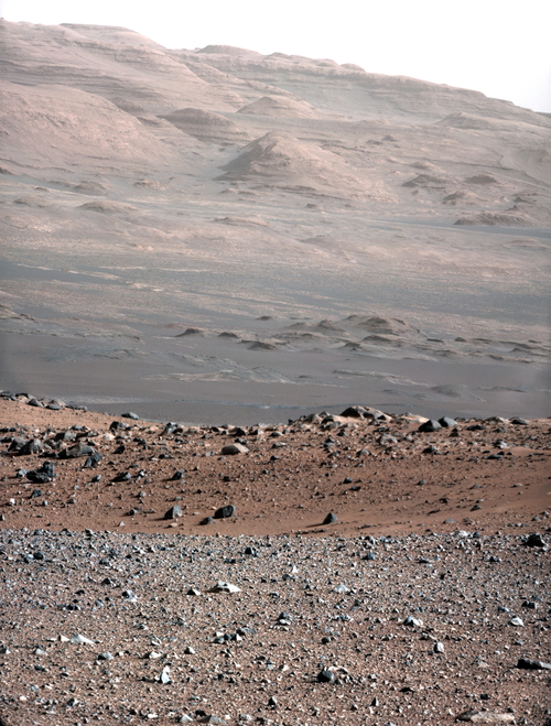 In this image released by NASA on Monday, Aug. 27, 2012, An image from a test series used to characterize the 100-millimeter Mast Camera on NASA's Curiosity rover taken on Aug. 23, 2012, looking south-southwest from the rover's landing site. The 100-millimeter Mastcam has three times better resolution than Curiosity's 34-millimeter Mastcam, though it has a narrower field of view. The gravelly area around Curiosity's landing site is visible in the foreground. Farther away, about a third of the way up from the bottom of the image, the terrain falls off into a depression (a swale). Beyond the swale, in the middle of the image, is the boulder-strewn, red-brown rim of a moderately-sized impact crater. Farther off in the distance, there are dark dunes and then the layered rock at the base of Mount Sharp. Some haze obscures the view, but the top ridge, depicted in this image, is 10 miles (16.2 kilometers) away. Scientists enhanced the color in one version to show the Martian scene under the lighting conditions we have on Earth, which helps in analyzing the terrain. (AP Photo/NASA/JPL-Caltech/MSSS)