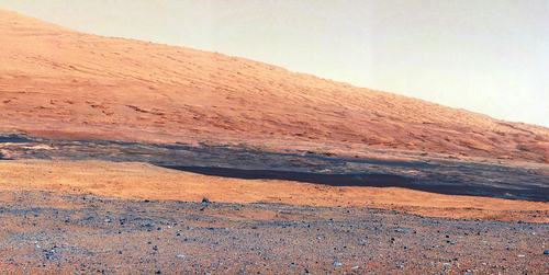 In this image released by NASA on Monday, Aug. 27, 2012, a photo taken by the Mast Camera (MastCam) highlights the geology of Mount Sharp, a mountain inside Gale Crater, where the rover landed. Prior to the rover's landing on Mars, observations from orbiting satellites indicated that the lower reaches of Mount Sharp, below the line of white dots, are composed of relatively flat-lying strata that bear hydrated minerals. Those orbiter observations did not reveal hydrated minerals in the higher, overlying strata. The MastCam data now reveal a strong discontinuity in the strata above and below the line of white dots, agreeing with the data from orbit. Strata overlying the line of white dots are highly inclined (dipping from left to right) relative to lower, underlying strata. The inclination of these strata above the line of white dots is not obvious from orbit. This provides independent evidence that the absence of hydrated minerals on the upper reaches of Mount Sharp may coincide with a very different formation environment than lower on the slopes. The train of white dots may represent an
