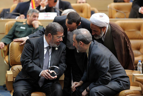 In this photo released by the official website of the Iranian presidency office, Egyptian President Mohammed Morsi, left, talks with Iranian officials during opening session of Nonaligned Movement, NAM, summit, in Tehran, Iran, Thursday, Aug. 30, 2012. Morsi described the Syrian regime as