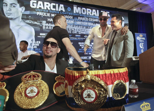 Danny Garcia, left foreground, super lightweight world boxing champion, is surrounded with his championship belts as Oscar De La Hoya, far right, president of Golden Boy Promotions, greets Brooklyn boxers Paulie Malignaggi, second from right, welterweight world champion, and Boyd Melson, a junior middleweight prospect, before a news conference on Thursday, Aug. 30, 2012, in Brooklyn, N.Y.  Golden Boy Promotions will presents the first boxing event at Brooklyn's new Barclays Center arena, headlining Garcia and Erik Morales in a championship match on Saturday, October 20.  (AP Photo/Bebeto Matthews)