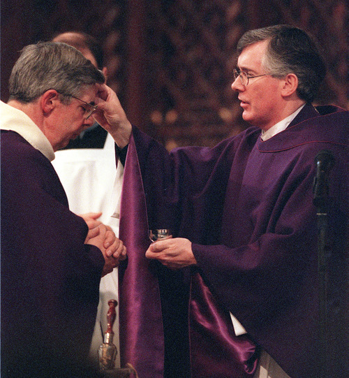 Monsignor M. Francis Mannion applies ash to the forehead of Deacon Owen Cummings at The Cathedral of the Madeline during their Ash Wednesday service. photo by Ryan Galbraith. 03/08/2000