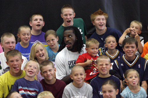 Francisco Kjolseth  |  The Salt Lake Tribune Silly faces all around, kids join Jazz forward DeMarre Carroll, center, for a group shot following Junior Jazz at the Trojan Century Center in Morgan, Utah on Monday, August 6, 2012. Dozens of boys and girls from all age groups had a chance to learn about the 6'8