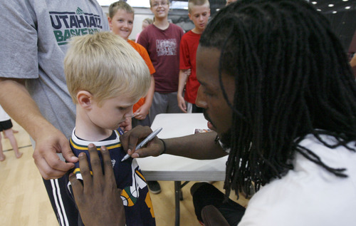 Francisco Kjolseth  |  The Salt Lake Tribune Jazz fan Nathan Pace, 5, of Morgan gets his shirt signed by Jazz forward DeMarre Carroll following Junior Jazz at the Trojan Century Center in Morgan, Utah on Monday, August 6, 2012. Dozens of boys and girls from all age groups had a chance to learn about the 6'8