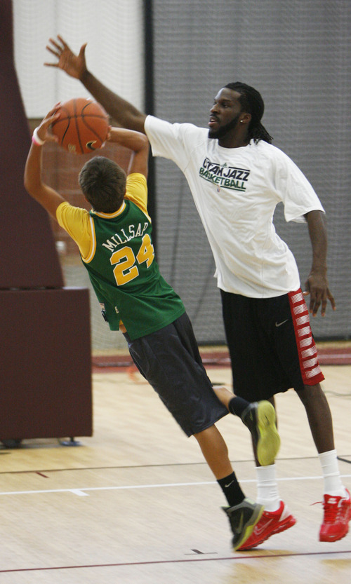 Francisco Kjolseth  |  The Salt Lake Tribune Trevor Rose, 13, of Morgan looks to try and get a shot past Jazz forward DeMarre Carroll as they have a one on one during Junior Jazz at at the Trojan Century Center in Morgan, Utah on Monday, August 6, 2012. Dozens of boys and girls from all age groups had a chance to learn about the 6'8