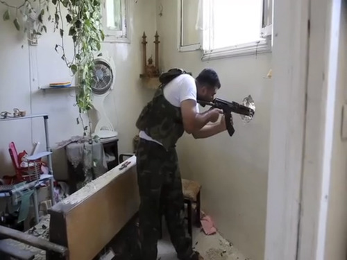 In this image made from video and accessed Saturday, Sept. 1, 2012, a Free Syrian Army fighter fires his weapon at a Syrian Army position through a hole in an empty and destroyed home during fighting in Aleppo, Syria. Syrian troops bombarded the northern city of Aleppo Saturday with warplanes and mortar shells as soldiers clashed with rebels in different parts of Syria's largest city, activists said. The Britain-based Syrian Observatory for Human Rights said the clashes were concentrated in several tense neighborhoods where some buildings were damaged and a number of people were wounded. (AP Photo/Robert King via AP video)
