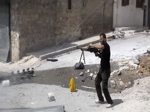 In this image made from video and accessed Saturday, Sept. 1, 2012, a Syrian rebel fires his weapon at Syrian Army positions during fighting in Aleppo, Syria. Syrian troops bombarded the northern city of Aleppo Saturday with warplanes and mortar shells as soldiers clashed with rebels in different parts of Syria's largest city, activists said. The Britain-based Syrian Observatory for Human Rights said the clashes were concentrated in several tense neighborhoods where some buildings were damaged and a number of people were wounded. (AP Photo/Robert King via AP video)