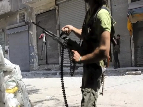In this image made from video and accessed Saturday, Sept. 1, 2012, Free Syrian Army fighters take up positions during fighting with Syrian troops in Aleppo, Syria. Syrian troops bombarded the northern city of Aleppo Saturday with warplanes and mortar shells as soldiers clashed with rebels in different parts of Syria's largest city, activists said. The Britain-based Syrian Observatory for Human Rights said the clashes were concentrated in several tense neighborhoods where some buildings were damaged and a number of people were wounded. (AP Photo/Robert King via AP video)