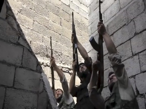 In this image made from video and accessed Saturday, Sept. 1, 2012, Free Syrian Army fighters raise their weapons during fighting with the Syrian Army in Aleppo, Syria. Syrian troops bombarded the northern city of Aleppo Saturday with warplanes and mortar shells as soldiers clashed with rebels in different parts of Syria's largest city, activists said. The Britain-based Syrian Observatory for Human Rights said the clashes were concentrated in several tense neighborhoods where some buildings were damaged and a number of people were wounded. (AP Photo/Robert King via AP video)