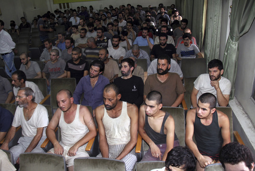 Syrian prisoners sit in a courtroom before their release in Damascus, Syria, Saturday, Sept. 1, 2012. Syria's official state news agency, SANA reported Saturday that 225 detainees, who took part in anti-government protests, were released. The amnesty by authorities is the second in a week as some 378 prisoners from Damascus and the central province of Homs, were freed on Monday. Rights activists say tens of thousands of Syrians have been detained over the past 18 months. (AP Photo/Bassem Tellawi)