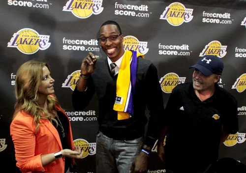 Dwight Howard, center, newly acquired by the Los Angeles Lakers from the Orlando Magic, holds up Jeanie Buss' 2002 championship ring as Buss, left, watches with Jim Buss, right, after a news conference in El Segundo, Calif., Friday, Aug. 10, 2012. (AP Photo/Los Angeles Times, Anne Cusack)