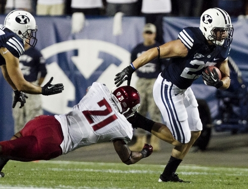 BYU's David Foote evades a tackle by Washington State's Eric Oertel during the first half of the NCAA college football game between the BYU Cougars and the Washington State Cougars at LaVell Edwards Stadium in Provo, Utah on Thursday, Aug. 30, 2012. (AP Photo/Spenser Heaps, Daily Herald)