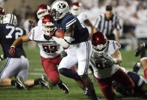 Kim Raff | The Salt Lake Tribune Brigham Young Cougars running back Jamaal Williams (21) makes a run as (left) Washington State Cougars linebacker Logan Mayes (83) and Washington State Cougars defensive tackle Steven Hoffart (94) make a tackle during BYU's home opener at LaVell Edwards Stadium in Provo, Utah on August 30, 2012.