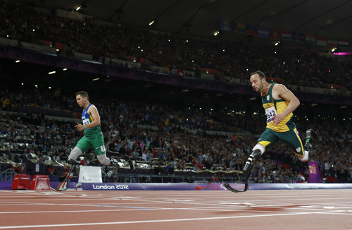 Brazil's Alan Fonteles Cardoso Oliveira, left, runs in to win the gold medal and beat South Africa's Oscar Pistorius, right, who took the silver medal in the men's 200m T44 category final during the athletics competition at the 2012 Paralympics, Sunday, Sept. 2, 2012, in London.  (AP Photo/Matt Dunham)