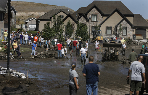 Scott Sommerdorf  |  The Salt Lake Tribune              The scene at the intersection of Apaloosa and Weatherby Drives in Saratoga Springs, Sunday, September 2, 2012, where hundreds of volunteers and neighbors pitched in to help those affected by the overnight flooding there.