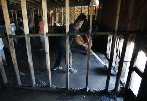 Scott Sommerdorf  |  The Salt Lake Tribune              Neighbors and other volunteers pitch in to help to muck out the unfinished basement of Russell Greene's home on Ruger Drive in Saratoga Springs, Sunday, September 2, 2012. The basement was full of a combination of mud and still-frozen hailstones about four feet deep.