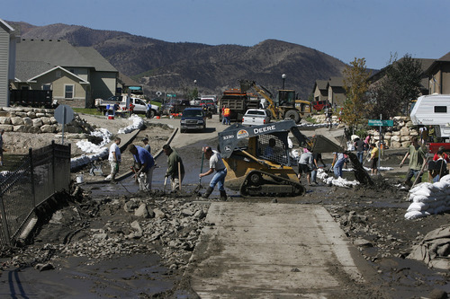 Scott Sommerdorf  |  The Salt Lake Tribune              Neighbors and other volunteers pitch in to help the homeowners affected by the flood near the intersection of Apaloosa and Weatherby Drives in Saratoga Springs, Sunday, September 2, 2012.