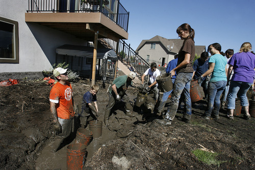 Scott Sommerdorf  |  The Salt Lake Tribune              Neighbors and other volunteers, incuding Jeff Newell at far left, pitch in to form a bucket line and clear mud for the homeowners at 2136 Weatherby Drive in Saratoga Springs, Sunday, September 2, 2012.