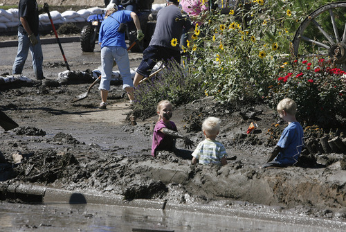 Scott Sommerdorf  |  The Salt Lake Tribune              Young children find fun in a mud fight while their parents volunteer to clean out homes affected by the floodimng near the intersection of Apaloosa and Weatherby Drives in Saratoga Springs, Sunday, September 2, 2012.