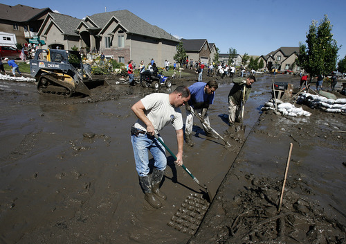Scott Sommerdorf  |  The Salt Lake Tribune              Neighbors and other volunteers work to direct mud into the storm drains  near the intersection of Apaloosa and Weatherby Drives in Saratoga Springs, Sunday, September 2, 2012.