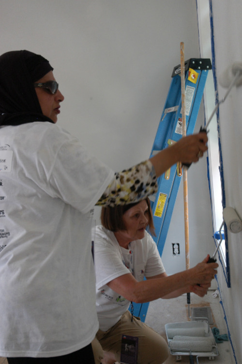 Noor Ul-Hasan, left,  and Gail Turpin paint a bedroom for the