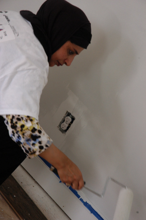 Noor Ul-Hasan, of Salt Lake City, helps paint a bedroom for the