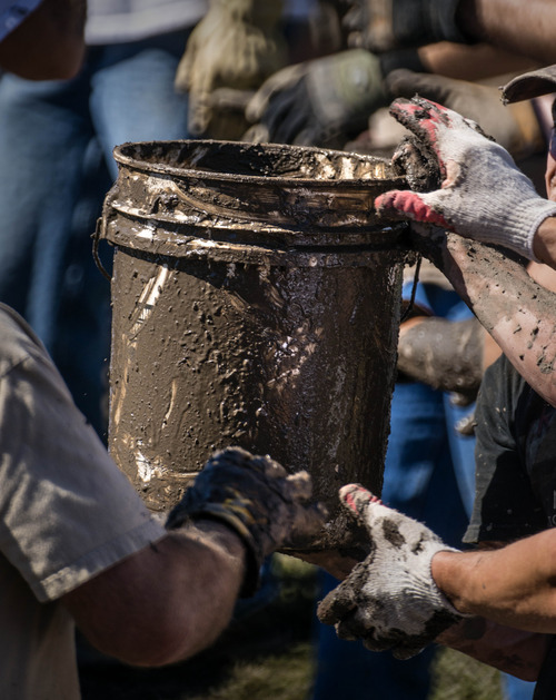 Douglas C. Pizac  |  Special to The SAlt Lake Tribune  Volunteers pass buckets of muddy water to each other from the basement to the street during the cleanup of a home flooded by hillside run off Monday, Sept. 3, 2012, in Saratoga Springs, Utah.