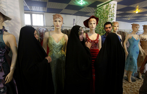 In this Sunday, Sept 2, 2012 photo, Iraqi women shop at a women's fashion store in Diwaniyah, 130 kilometers (80 miles) south of Baghdad, Iraq. A new culture rift is emerging in Iraq, as young women replace shapeless cover-ups with ankle-baring skirts and tight blouses, while men strut around in revealing slacks and spiky haircuts. The relatively skimpy styles have prompted Islamic clerics in at least two Iraqi cities to mobilize the