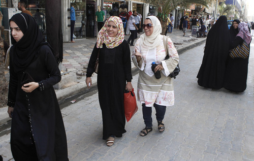 Iraqi women shop at a marketplace in northern Baghdad's Kazimiyah neighborhood , Iraq, Sunday, Sept. 2, 2012.  A new culture rift is emerging in Iraq and, largely, at the seat of one of Shiite Islam's holiest sites as young women doff their shapeless cover ups and men strut around in revealing slacks and edgy haircuts. This has prompted clerics to mobilize the fashion police in the name of protecting the Islamic nation's heritage. (AP Photo/Karim Kadim)