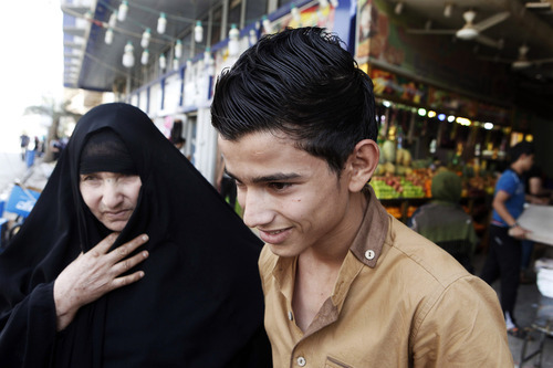 A mother with her young son shop at a market place in northern Baghdad's Kazimiyah neighborhood , Iraq, Sunday, Sept 2, 2012. A new culture rift is emerging in Iraq and, largely, at the seat of one of Shiite Islam's holiest sites as young women doff their shapeless cover-ups and men strut around in revealing slacks and edgy haircuts. This has prompted clerics to mobilize the fashion police in the name of protecting the Islamic nation's heritage. (AP Photo/Karim Kadim)