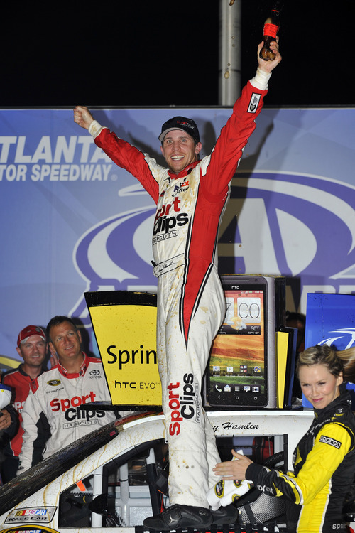Denny Hamlin celebrates the win after the NASCAR Sprint Cup Series auto race at Atlanta Motor Speedway, Sunday, Sept. 2, 2012, in Hampton, Ga. (AP Photo/Autostock, Nigel Kinrade) MANDATORY CREDIT