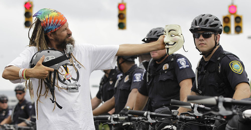 An Occupy Demonstrator takes a photo with his mask during an unscheduled protest march, Tuesday, Sept. 4, 2012, in Charlotte, N.C. The Democratic National Convention begins today.  (AP Photo/Chuck Burton)