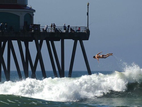 A surfer gets some air as he bails out of a wave during a Labor Day outing next to the Huntington Beach Pier Monday, Sept. 3, 2012 in Huntington Beach, Calif. (AP Photo/The Orange County Register, Kevin Sullivan)