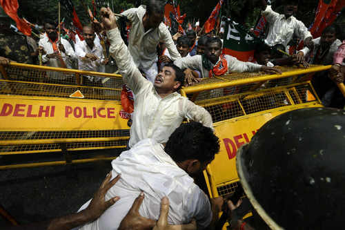 Supporters of India's main opposition Bharatiya Janata Party (BJP) push through a barricade during a demonstration in favor of carving a separate state of Telangana from Andhra Pradesh state, in New Delhi, India, Tuesday, Sept. 4, 2012. Supporters of the new Telengana state have complained their area in the north was underdeveloped and ignored by powerful politicians from southern Andhra Pradesh. Demands for a separate state have erupted sporadically since the 1950s. (AP Photo/Saurabh Das)