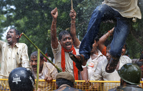Supporters of India's main opposition Bharatiya Janata Party (BJP) shout slogans as police use a water cannon to disperse them during a demonstration in favor of carving a separate state of Telangana from Andhra Pradesh state, in New Delhi, India, Tuesday, Sept. 4, 2012. Supporters of the new Telengana state have complained their area in the north was underdeveloped and ignored by powerful politicians from southern Andhra Pradesh. Demands for a separate state have erupted sporadically since the 1950s. (AP Photo/Saurabh Das)