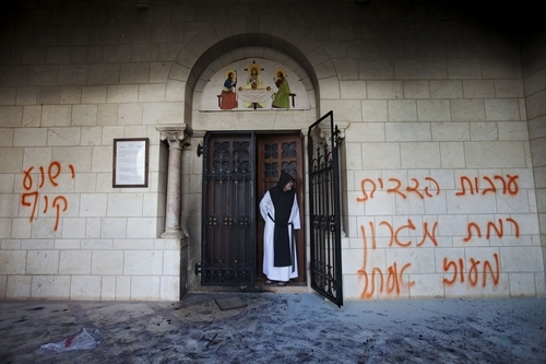 A catholic monk stands in a doorway of the Latrun Trappist Monastery where Israeli police say vandals overnight have spray-painted anti-Christian and pro-settler graffiti and set the monastery's door on fire, in Latrun, between Jerusalem and Tel Aviv, Israel, Tuesday, Sept 4, 2012. Suspicion fell on Jewish settlers and their supporters who retaliate against anti-settlement measures, generally by attacking Palestinian property, but also by vandalizing Christian sites and Israeli military facilities. Earlier this week, the government ordered settlers out of two unauthorized enclaves in the West Bank. Some of the graffiti referred to unauthorized settler outposts and one read,