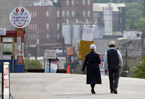 An Amish man and woman walk through a parking lot after leaving the U.S. courthouse in Cleveland Wednesday, Sept. 5, 2012. Sixteen members of a breakaway Amish sect in Bergholz, Ohio, led by Sam Mullet, are on trial, accused of planning and taking part in the attacks targeted the hair and beards of Amish bishops. (AP Photo/Mark Duncan)