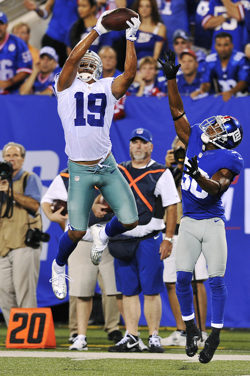 Dallas Cowboys wide receiver Miles Austin (19) catches a pass over New York Giants defensive back Justin Tryon (30) during the second half of an NFL football game, Wednesday, Sept. 5, 2012, in East Rutherford, N.J. Austin scored a touchdown on the play. (AP Photo/Bill Kostroun)