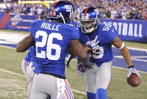 New York Giants linebacker Michael Boley (59) celebrates with teammate  Antrel Rolle (26) after intercepting a pass during the first half of an NFL football game against the Dallas Cowboys Wednesday, Sept. 5, 2012, in East Rutherford, N.J. (AP Photo/Bill Kostroun)